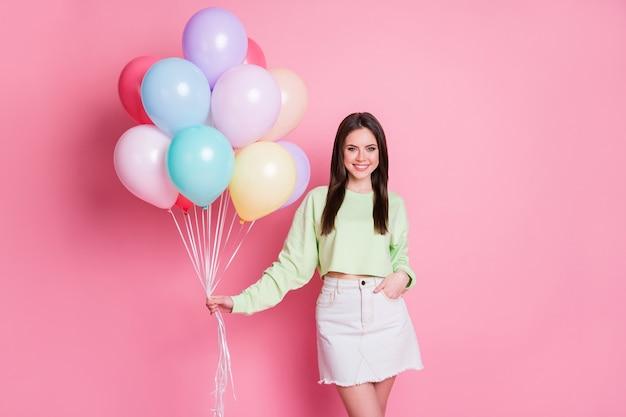 Photo d'une jolie dame joyeuse organiser une fête d'anniversaire surprise pour le meilleur ami tenir de nombreux ballons à air porter des jeans pull vert décontracté mini jupe isolé fond de couleur pastel rose