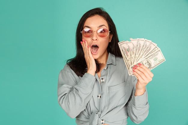 Photo de jolie dame à lunettes de soleil est surpris de l'argent