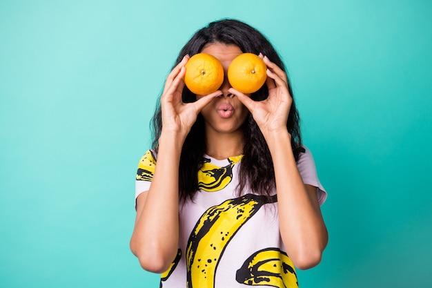 Photo de jolie dame noire tenir deux oranges couvrir les yeux porter un t-shirt imprimé banane isolé sur fond de couleur sarcelle