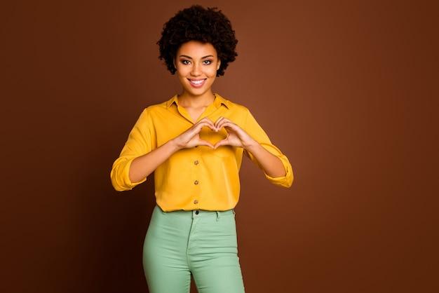 Photo de jolie dame ondulée de la peau foncée tenant les doigts des bras en forme de coeur symbolisant le concept de soins de santé cardiaques sains porter chemise jaune pantalon vert isolé couleur marron