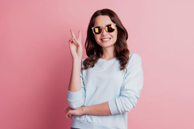 Photo de jolie dame sympathique sourire blanc brillant spectacle v-sign en lunettes de soleil sur fond rose