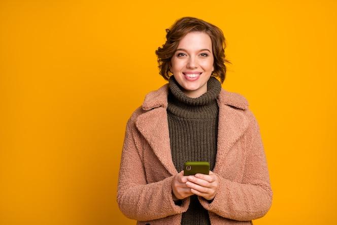 Photo de jolie dame tenir téléphone populaire instagram blogger voyageur porter manteau de style moderne décontracté pull vert chaud col tricoté