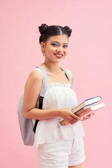 Photo d'une jolie étudiante de 20 ans avec une coiffure à double pain portant un sac à dos tenant de nombreux livres d'étude isolés sur fond rose