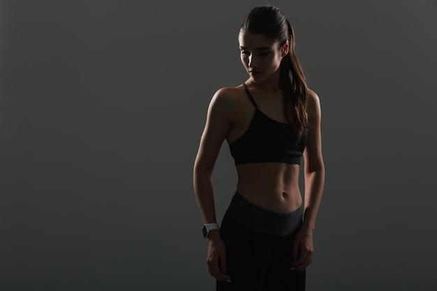 Photo de jolie femme athlétique regardant de côté tout en posant avec une montre-bracelet, isolée sur un mur sombre