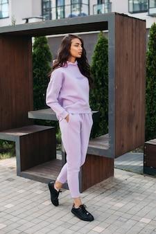 La photo d'une jolie femme caucasienne en costume de sport violet et de baskets noires garde ses mains dans les poches