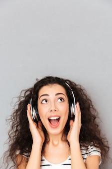 Photo de jolie femme caucasienne en t-shirt rayé appréciant la musique via un casque moderne étant isolé sur mur gris