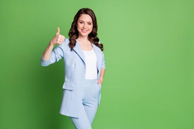 Photo d'une jolie femme coiffure frisée montrer le pouce vers le haut de la poche à main porter un blazer bleu fond de couleur vert isolé