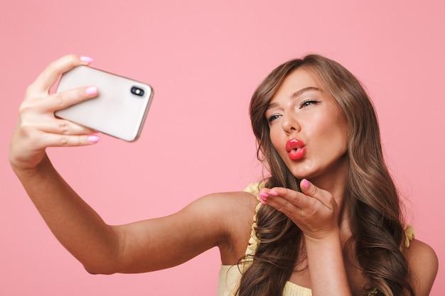 Photo de jolie femme sexuelle des années 20 avec de longs cheveux bruns souriant et donnant l'air baiser à la caméra tout en prenant selfie sur téléphone mobile, isolé sur fond rose