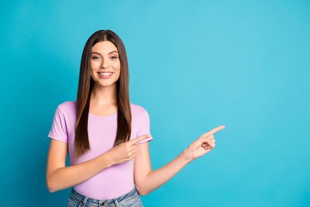 Photo d'une jolie femme souriante portant un t-shirt violet décontracté pointant deux bras doigts espace vide isolé fond de couleur bleu