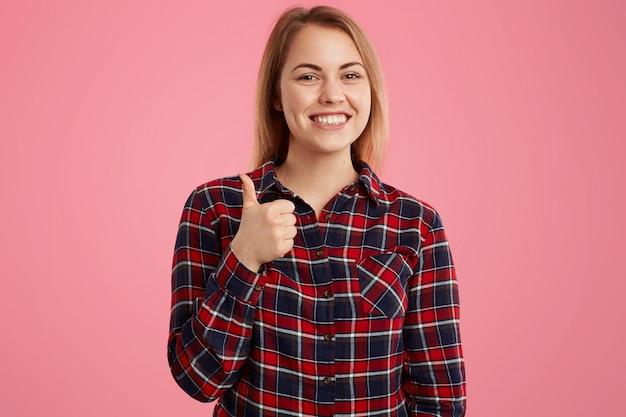 Photo de jolie femme avec un sourire à pleines dents, vêtue d'une chemise à carreaux, garde le pouce levé, donne son approbation à quelque chose