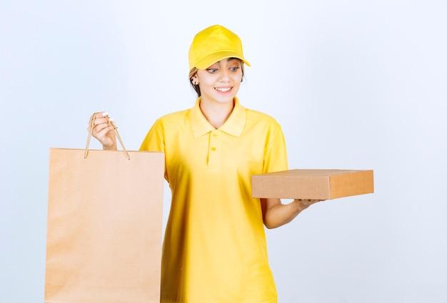 Photo d'une jolie femme en uniforme jaune tenant une boîte et un sac en papier kraft vierge marron.