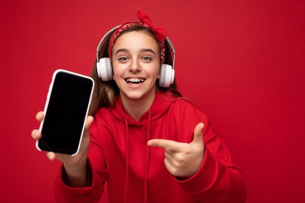 Photo d'une jolie fille brune souriante positive portant un sweat à capuche rouge isolé sur fond rouge tenant