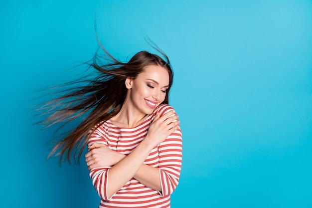 Photo d'une jolie fille charmante au contenu s'amuser concept d'amour câlin câlin yeux fermés coupe de cheveux mouche vent air porter chemise blanche isolée sur fond de couleur bleu
