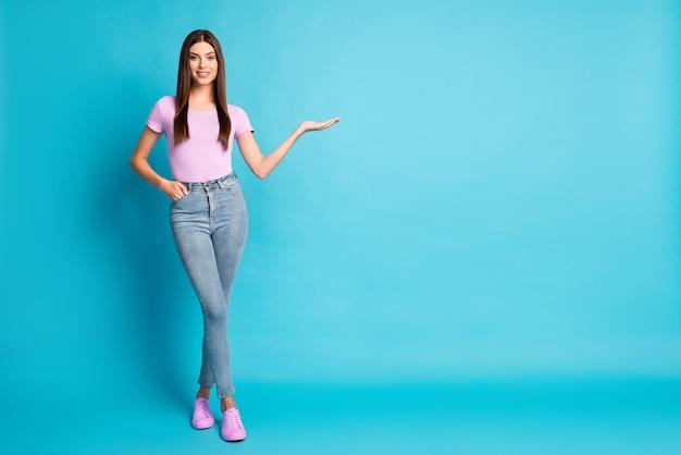Photo de jolie fille étudiante porter des jeans t-shirt violet décontracté bras pointé espace vide isolé fond de couleur bleu