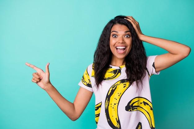 Photo d'une jolie fille excitée tête de bras indiquer l'espace vide du doigt porter un t-shirt imprimé banane isolé sur fond de couleur sarcelle