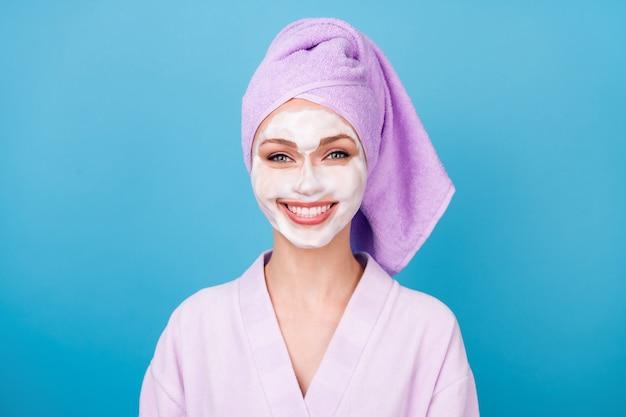 Photo de jolie fille masque en mousse pour le visage sourire blanc brillant porter une serviette violette turban peignoir isolé fond de couleur bleu