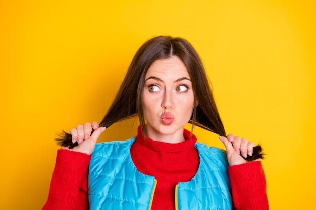 Photo d'une jolie fille mignonne toucher sa coupe de cheveux profiter de cheveux soyeux et lisses regarder copypace envoyer un baiser d'air porter des vêtements de saison isolés sur fond de couleur brillant brillant
