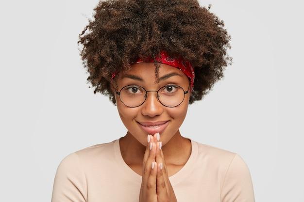 Photo d'une jolie fille à la peau foncée qui garde les mains près de la bouche, regarde directement
