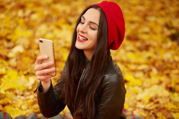 Photo de jolie fille portant un béret rouge et une veste en cuir noir dans le parc en automne, faisant l'autoportrait sur son téléphone portable