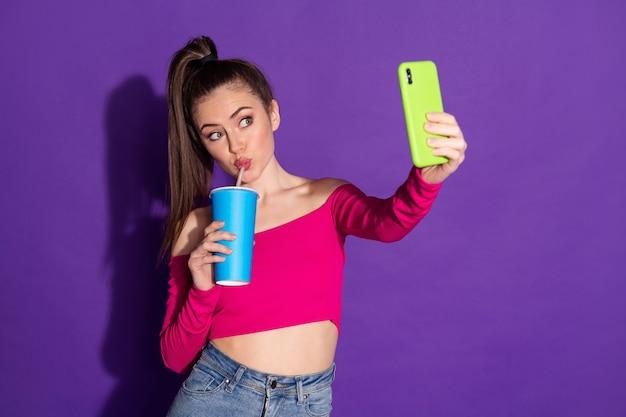 Photo d'une jolie fille tenir une tasse de téléphone faire des selfies porter des jeans roses épaules nues haut isolé sur fond de couleur violette