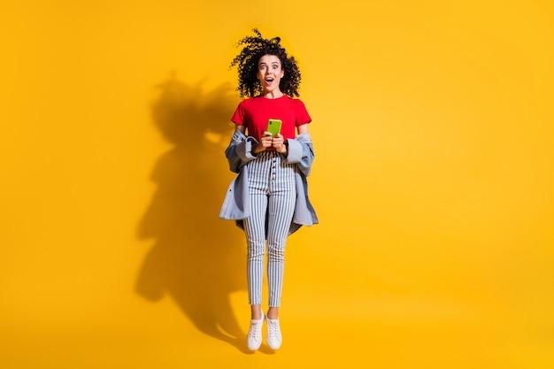 Photo de jolie fille tenir le téléphone bouche ouverte sauter porter un jean rayé recadrée t-shirt rouge veste baskets isolé fond de couleur jaune