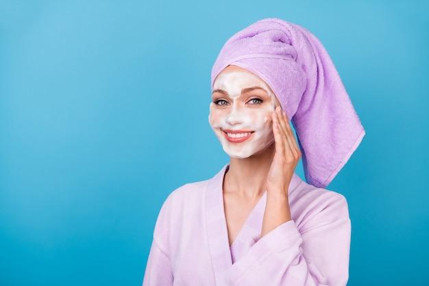 Photo de jolie fille utiliser un masque de beauté blanc palm joue porter une serviette violette turban peignoir isolé fond de couleur bleu