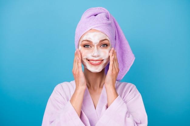 Photo de jolie fille utiliser un masque en mousse mains pommettes porter une serviette violette turban peignoir isolé fond de couleur bleu