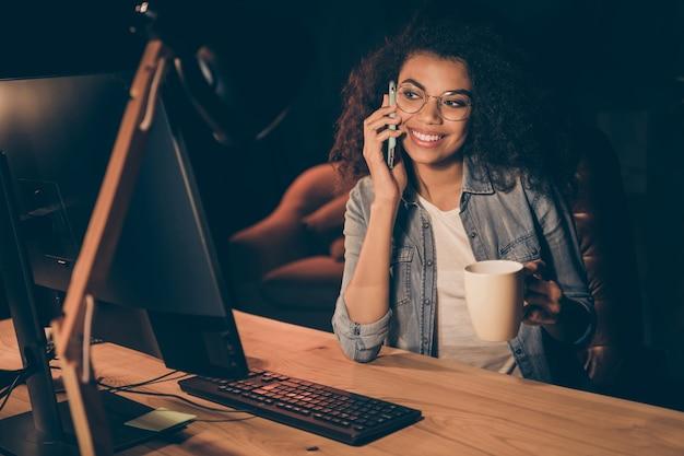 Photo de jolie jeune femme d'affaires regarder moniteur boire café chaud parler téléphone