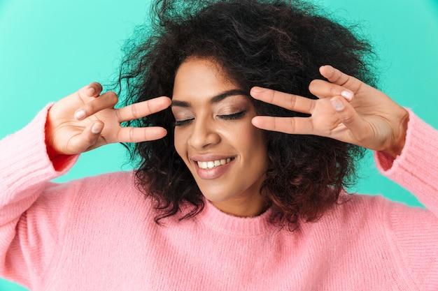 Photo de jolie jeune femme des années 20 souriant et montrant le signe de la paix à deux mains, isolé sur mur bleu