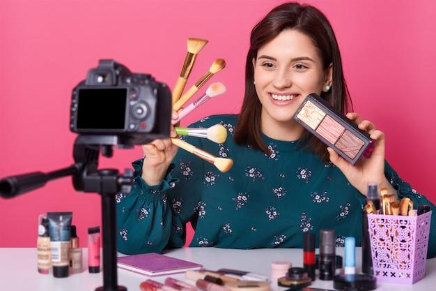 Photo d'une jolie jeune femme brune fait un didacticiel vidéo avec un appareil photo numérique moderne