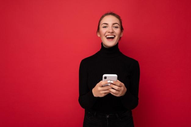 Photo d'une jolie jeune femme brune positive portant un pull noir isolé sur rouge