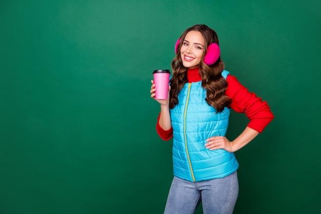 Photo d'une jolie jeune femme charmante à la main boire un café savoureux à emporter en attendant un ami à pied parc de soirée d'hiver porter des cache-oreilles roses gilet bleu pull rouge isolé fond de couleur verte