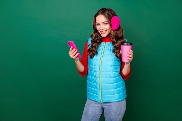 Photo d'une jolie jeune femme charmante tenant une tasse de café à emporter rayonnante souriante connexion réseau social surf porter des cache-oreilles roses gilet bleu pull rouge isolé fond de couleur verte