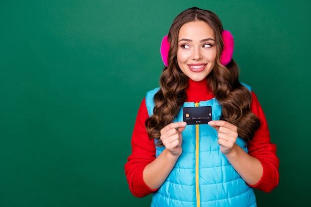 Photo d'une jolie jeune femme charmante tenir une carte de crédit intéressée regarder copyspace présentant une bonne variante souriant porter des cache-oreilles roses gilet bleu pull rouge isolé fond de couleur verte