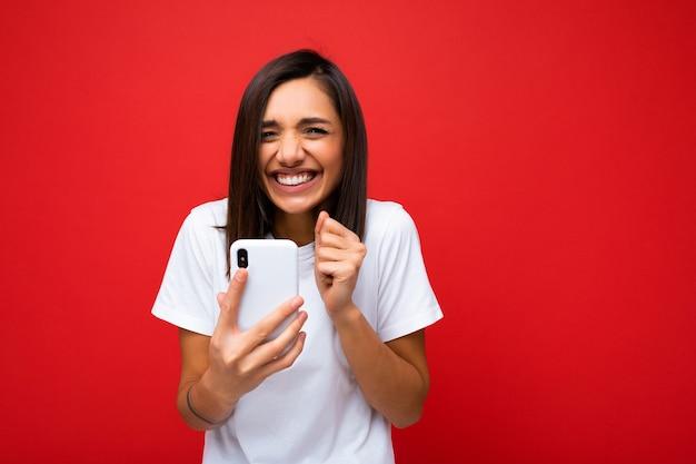 Photo d'une jolie jeune femme heureuse, joyeuse et positive, vêtue d'une tenue élégante et décontractée, isolée sur fond avec un espace vide tenant à la main et utilisant la messagerie par téléphone mobile s