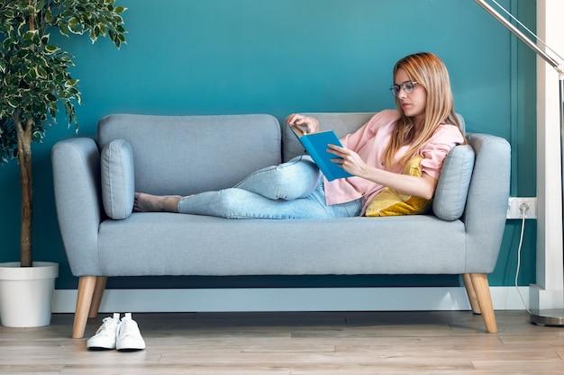 Photo d'une jolie jeune femme lisant un livre allongée sur un canapé à la maison.
