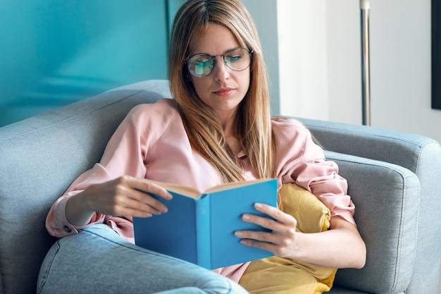 Photo d'une jolie jeune femme lisant un livre assis sur un canapé à la maison.