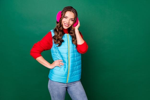 Photo de jolie jeune femme mains hanche rayonnant brillant souriant café chaud hiver porter des cache-oreilles roses jeans gilet zippé bleu pull rouge isolé fond de couleur verte