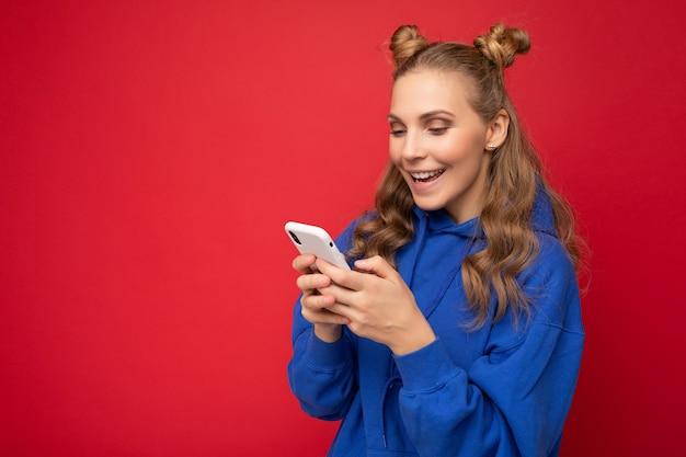Photo d'une jolie jeune femme positive et séduisante portant une tenue élégante décontractée isolée sur fond avec un espace vide tenant dans la main et utilisant des sms de messagerie pour téléphone portable en regardant