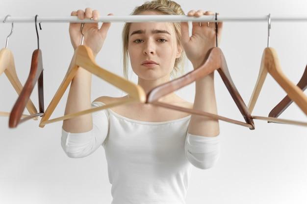 Photo de jolie jeune femme de race blanche en haut blanc posant au rail avec des cintres vides, ayant une expression faciale triste bouleversée parce qu'elle n'avait rien à porter. les gens, les vêtements, le style et la mode