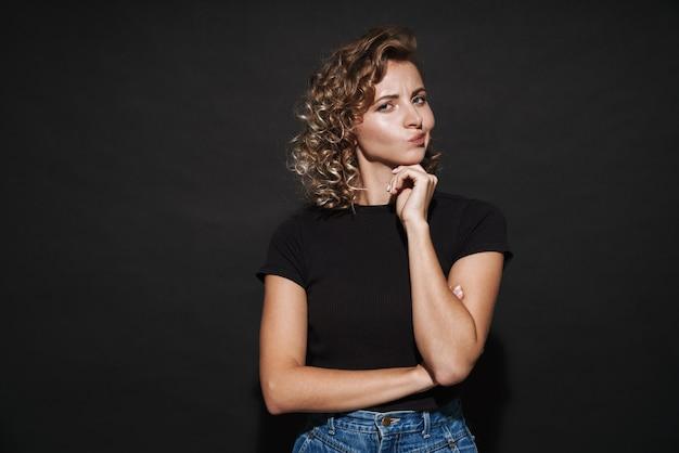 Photo d'une jolie jeune femme réfléchie et réfléchie isolée sur un mur gris foncé regardant de côté.