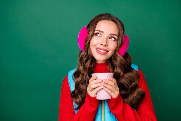 Photo d'une jolie jeune femme rêveuse et mignonne tenant une tasse de boisson au cacao rechercher un espace vide souriant fantasmer des vacances d'été porter des cache-oreilles roses gilet bleu pull rouge isolé fond de couleur verte