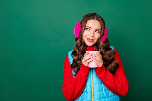 Photo d'une jolie jeune femme rêveuse tenant une tasse boire du thé chercher un espace vide imaginer une fête à thème de noël porter des cache-oreilles roses gilet bleu pull rouge isolé fond de couleur verte