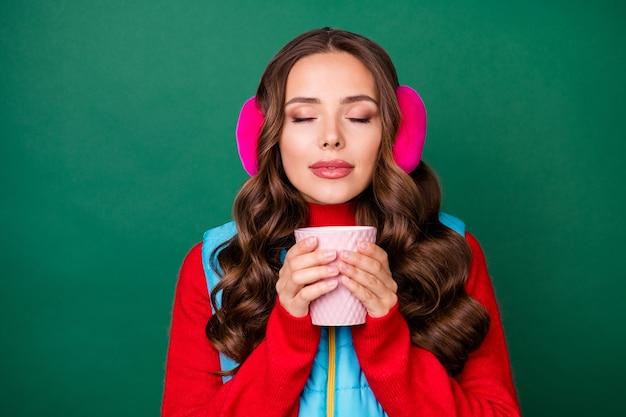 Photo d'une jolie jeune femme rêveuse tenant une tasse de café fermer les yeux sentant la saveur parfaite porter des cache-oreilles roses gilet zippé bleu pull rouge isolé fond de couleur verte