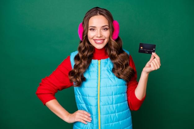 Photo d'une jolie jeune femme souriante montrant une carte de crédit à la main promotion de la banque de la hanche dépôt rentable épargne porter des cache-oreilles roses gilet bleu pull rouge isolé fond de couleur verte