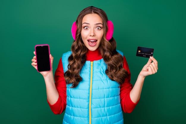 Photo d'une jolie jeune femme souriante montrant une carte de crédit par téléphone regard choqué achats en ligne vente remises porter des cache-oreilles roses gilet bleu pull rouge isolé fond de couleur verte