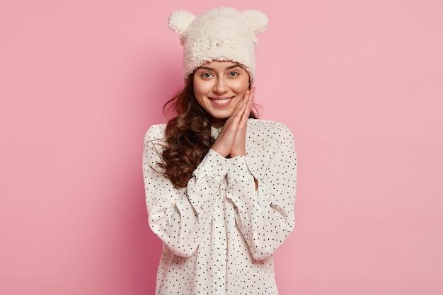 Photo de jolie jeune femme avec un sourire sincère à pleines dents, garde les mains près du visage, se sent heureuse et ravie, porte un chapeau d'hiver chaud drôle avec des oreilles, démontre une nouvelle marque de vêtements cette saison