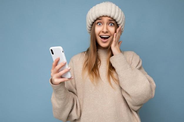 Photo d'une jolie jeune femme surprise folle et étonnée portant des vêtements décontractés et élégants, isolée sur fond avec espace de copie tenant et utilisant un téléphone portable regardant la caméra