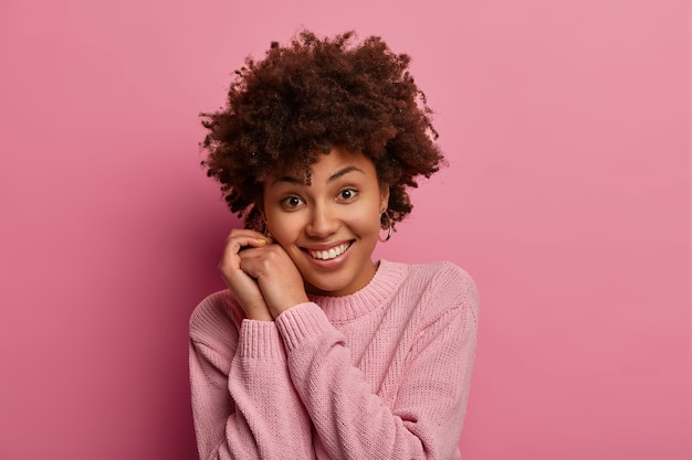 Photo de jolie jeune femme tendre aux cheveux afro sourit doucement, garde les mains près du visage, regarde directement, porte un pull décontracté, entend quelque chose de bien, pose contre le mur rose