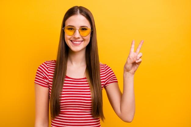 Photo d'une jolie jeune fille insouciante, coiffure longue, spectacle souriant, signe v, accueillant les gens, fête des étudiants, vêtements de soleil, chemise rouge blanche rayée, fond de couleur jaune vif